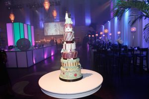 """""""Fun - whimsical and tall - the marzipan bride and groom and marzipan kids adorned the cake on different tiers."""""""